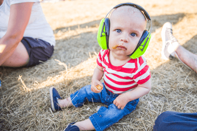 Kid at festival wearing ear defenders