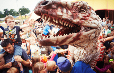 Image of kids at a festival with a dinosaur