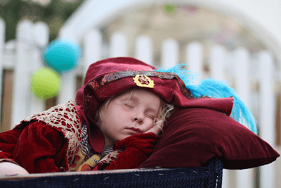 Image of a tuckered out kid at a festival