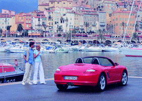 Image of couple looking at a Porsche Boxster