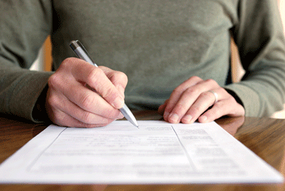 Image of man signing logbook loan contract