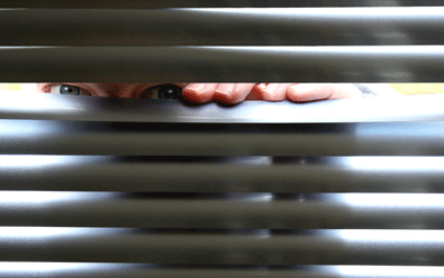 Image of a man looking through blinds