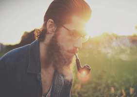 Hipster with beard smoking a pipe