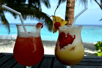 Image of two fruity cocktails on a table by the beach