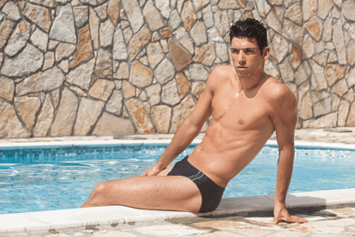 Image of a man relaxing by the pool wearing a pair of Speedos