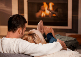 Image of a couple curled up in front of a log fire
