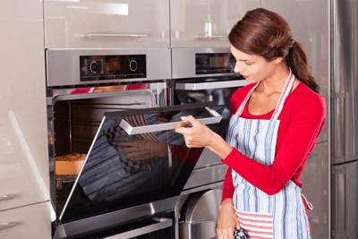 Image of a woman opening an oven door to glance at a pie