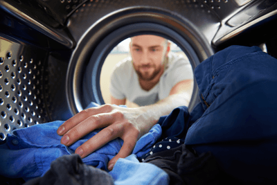 Image of a man reaching into a washing machine