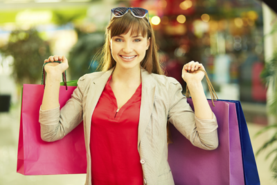 Image of a lady holding multiple shopping bags and smiling with glee