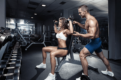 Image of a buff man and woman lifting weights in the gym