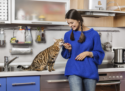 Image of a woman fussing over her cat in a kitchen