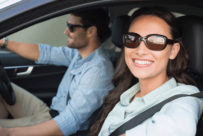 Image of a couple wearing sunglasses while driving