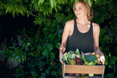 Image of a healthy looking lady with a box of greens