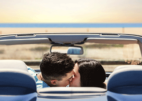 Image of canoodling couple in car