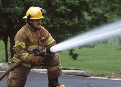 Image of a firefighter pointing his hose