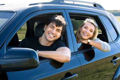 Image of two happy looking people driving