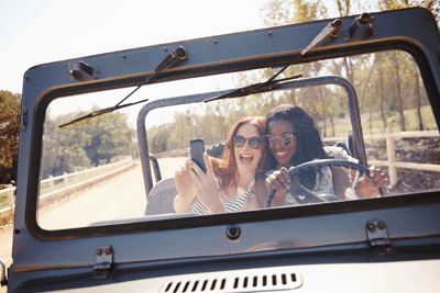Image of two women taking a selfie while driving (not advised)