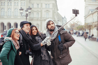 Image of a group of friends using a selfie stick