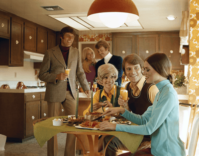 Image of a group of retro firends enjoying a '70s style kitchen