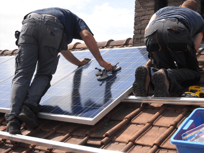 Image of two men fitting solar panels to a roof