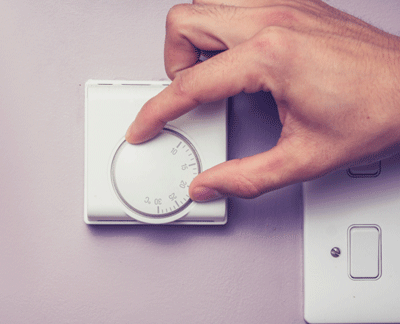 Image of a hand turning down a thermostat