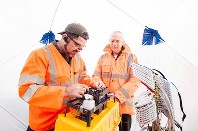 Image of people working on broadband equipment