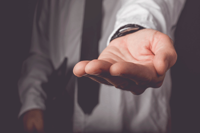 Image of a man sticking out his hand for money