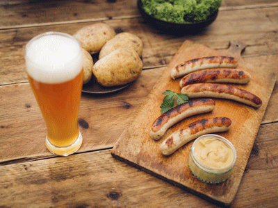 Image of a German Sausage platter, accompanied by mustard and weissbier