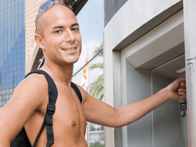 Man on holiday at a cash machine
