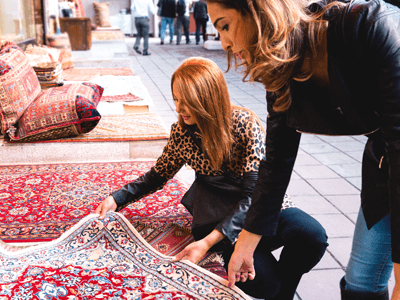 Two women shopping for rugs in a souq