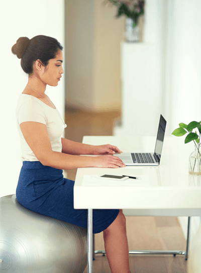 Image of a woman sitting on an exercise ball at her desk