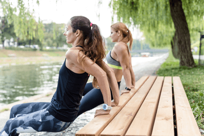 Image of two women doing tricep dips using a park bench