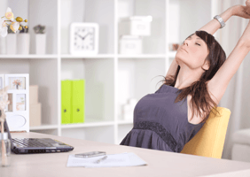 Image of a woman stretching at her desk