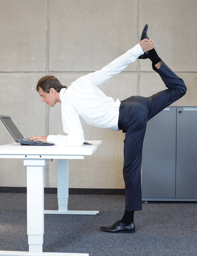 Image of a man doing a yoga pose at a standing desk