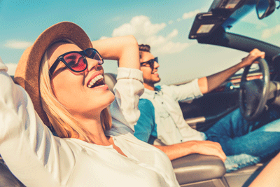 Image of couple enjoying a drive in the sun