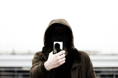 Image of a hooded figure taking a selfie