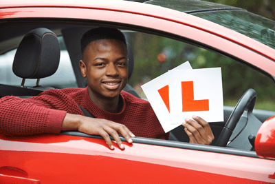 A young learner driver holding l plates