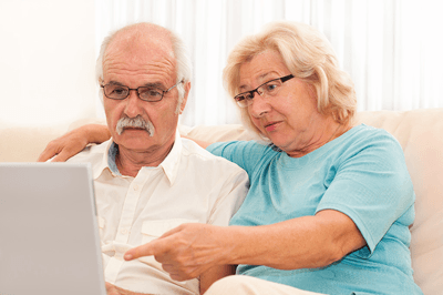 Older couple looking at their laptop and looking annoyed