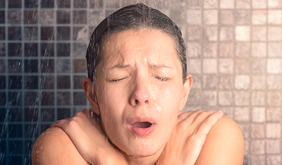Woman surprised by a cold shower