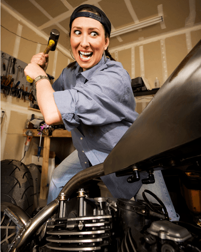 A woman attacking a motorbike with a hammer