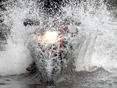 A motorbike going through a very large puddle