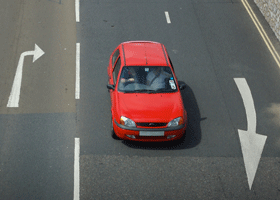 Image of a red Ford Fiesta at a cross roads