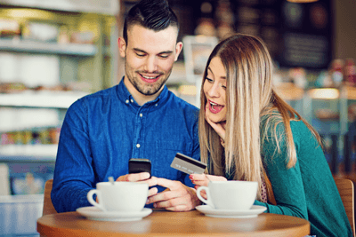 Image of a couple holding a credit card looking at a phone