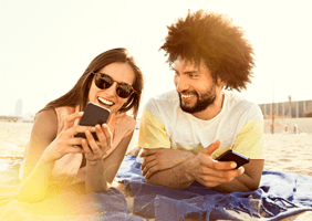 Image of a couple looking at a phone on the beach