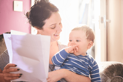 A woman looking at bills with her baby