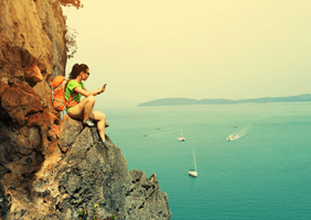 Image of a woman using her phone on the edge of  a cliff