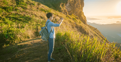 Image of a boy using his phone by a cliff edge