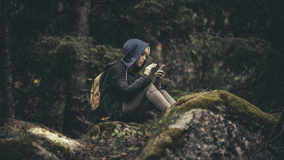 Image of a youth using their phone in a secluded forest