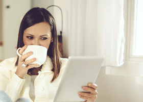 Image of a woman looking cosy drinking a cup of tea
