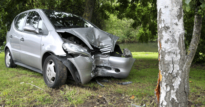 image of a car crashed next to a tree